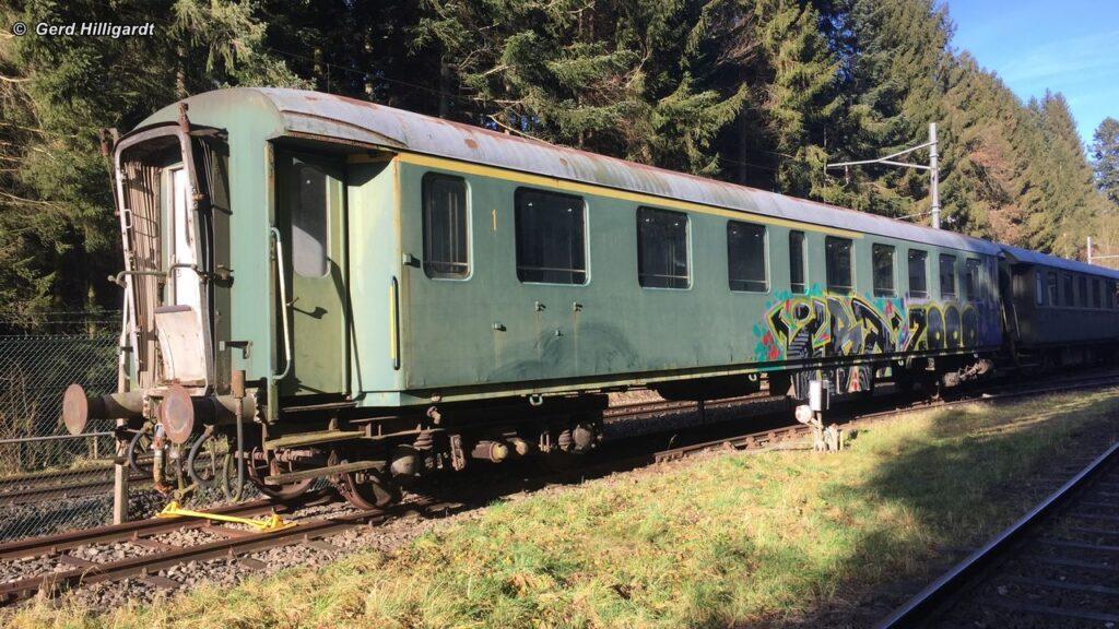 """Historischer Reisezugwagen der SBB, Typ RIC Umbau 1957 steht in abgeschossenem grün und unrenoviert in der Abstellanlage """"Huttwil Wald""""."""